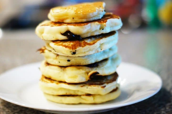 A stack of fat fluffy pancakes on a white plate with a blurred out background.